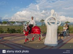 Download this stock image: A man on a gray horse in motion, advertises goods…