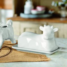 """Spread country style! Butter dish is made from high-quality porcelain in the shape of a pastoral country cow. Add a touch of rustic farmhouse charm to your dinner table. 4.5""""H x 7""""L"""