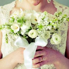 Soft and romantic bouquet consists of white freesias, white ranunculus, white lilacs and white feathers woven around the bouquet…