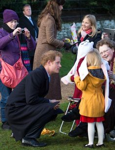 Prince Harry talking to a young fan at the annual Christmas Day church service.12/25/2014