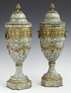 Pair Of Louis XV Style Gilt Bronze Mounted Highly Figured Marble Covered Urns, The Top With An Artichoke Finial Over A Pierced Bronze Band With Ring Handles, Above A Leaf Form Garland, On A Shaped Base On A Bronze Plate   c. Late 19th Century