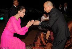 Honoured: The actress - who has kept a low profile of late since filing for divorce from Brad Pitt in September - looked sensational as she took a step out of her usual muted fashion toned choices for a hot pink gown in the country's Siem Reap province