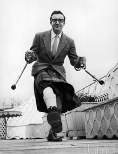 April 1963: Full-length image of British actor and comedian Peter Sellers, dressed in a kilt, doing a jig with crutches after breaking his ankle while getting into his car. (Photo by Express/Express/Getty Images)