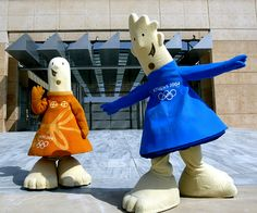 Phevos, right, and Athena, the official Athens 2004 Olympic Games mascots, wave in front of a monument at the beginning of the Marathon race route in Athens on July 26, 2004. (Photo by Stringer/Reuters)