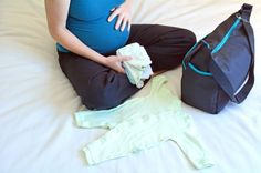 Pregnancy - pregnant woman packing a Hospital Bag. Concept photo of pregnant women life style and health care. copy space