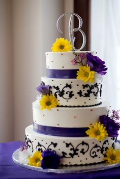 White wedding cake with black detail, accented with yellow and purple flowers, and topped off with an initial cake topper
