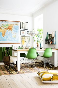 Lime green dining space with a map of the world on the wall and small wall storage
