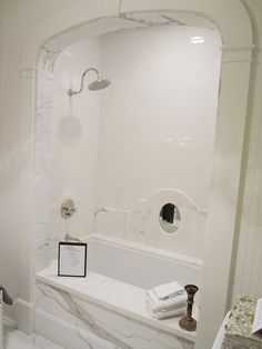 love the white beadboard paneled walls, a simple white hexagon marble mosaic on the floor, a white carrara marble bath with an arch via Cococozy