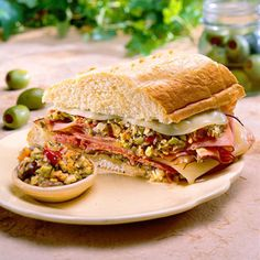 Muffulettas | Originating in New Orleans, the Muffuletta is a staple for Mardi Gras celebrations. It is made with an Olive Spread of herbs and vegetables that is slathered on ham, salami, and provolone cheese.