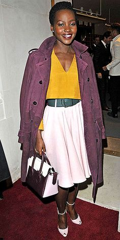 """It's the dilemma many a fashionista is facing this fall: If the crop top trend is here to stay, how does one make it seasonally appropriate? Follow Lupita's steps: 1. Pick a long-sleeve version in a hue that conjures up a feeling of autumn leaves. 2. Accessorize the look with a mix of rich tones. 3. Swipe on a berry lip. When all else fails, that's a surefire way to say """"fall."""""""