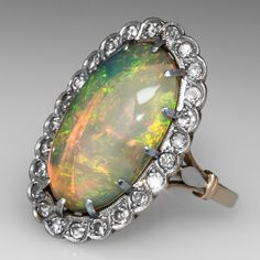 Victorian Jelly Opal Cocktail Ring. This magnificent antique Victorian opal cocktail ring is centered with a certified non-enhanced 4.76 carat natural jelly opal cabochon. The opal is breathtaking with green, yellow, and orange fire color, a broad flash fire pattern, strong brilliance, and vitreous luster. The opal's symmetry is very good and it's polish rating is excellent. Accenting the opal is a halo of round single cut high quality diamonds finished with milgrain edging