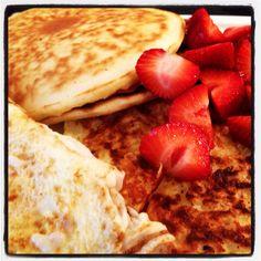 Pancakes, potato pancakes, eggs and strawberries at home.