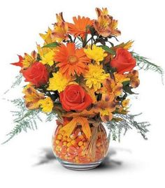 Fall flower arrangement. Love the candy corn as a filler. cute idea.