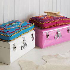 Malas antigas usadas como banquetas com almofadas decoradas