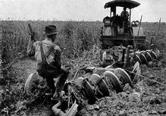 Early 20th-century image of a tractor ploughing an alfalfa field in Iowa.