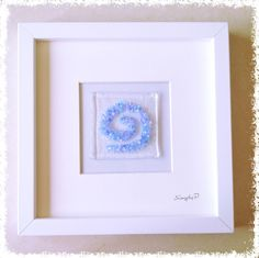 "Glass Fused Wall Art - Celtic Swirl. SimplyP Glass Studio design and make a range of glass fused wall art in Dublin, Ireland. Glass Pictures This item is made by hand and contains layers of glass and frit which is tack fused in a glass kiln. You can touch and feel the object. The glass picture is 3""x3"" and frame is 8""x8"" Each glass picture is unique and may differ slightly."