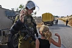 A Palestinian girl tries to punch an Israeli soldier during a protest against the expansion of the nearby Jewish settlement of Halamish.  Image by Majdi Mohammed / AP