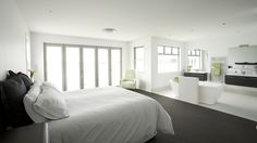 This master bed suite has an open design with the change from carpet to tiles the only distinguisher from bed to bath.