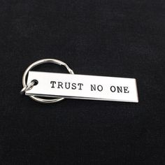 """This """"Trust No One"""" key chain is hand stamped with care, one letter at a time…"""