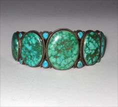 """high grade turquoise (five large oval stones with eight teardrop smaller stones) and coin silver circa 1920s-1930s inside dimensions: 2 1/16"""" diameter x 1 7/8"""" from the center to the opening ; the opening width is 1 5/8"""" excellent condition (one stone has a crack but the crack is very stable) ex: Everett and Martha Thomas Collection $2400. (J2102)"""