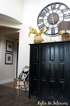 Entryway AFTER!  With large clock, black armoire for kids coat and shoe storage, artwork and décor with Benjamin moore cream paint colour