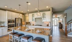 Three pendant lamps and glass fronted cabinets are memorable touches. The Santa Clara plan built by K. Hovnanian Homes at Brynwood. Minneapolis, MN.