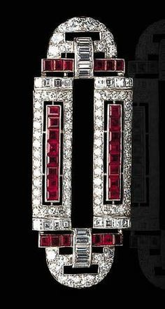 AN ART DECO RUBY AND DIAMOND BROOCH - The geometric openwork plaque, set with old European and baguette-cut diamonds, accented by calibré-cut rubies, mounted in platinum, circa 1925
