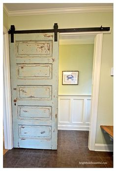 This reclaimed wooden door offers a nice division in between rooms. I am loving the mint green color choice too.