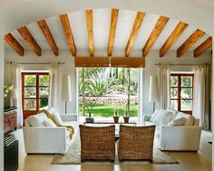 Love all this.  The ceiling beams are great.  I like the contemporary couch paired with the wicker chairs.