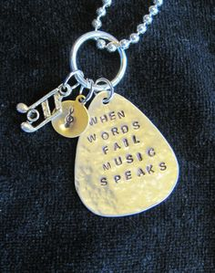 """Along with music notes and a small brass disc personalized with an initial, a recycled aluminum guitar pick says, """"When words fail music speaks"""". Let the music speak on this pendant that is suspended from an 18-inch ball chain necklace. This necklace is part of a fundraiser for our high school: 25% of the sale of this necklace will go to support our High School Band!"""