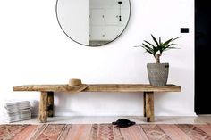 my scandinavian home: bench and round mirror in the hallway of a sleek and rustic in a Sydney bachelor pad