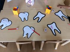 Dentist teeth healthy eating theme people who help us topic mark making activity laminated teeth and dry wipe markers with toothbrushes to clean teeth EYFS