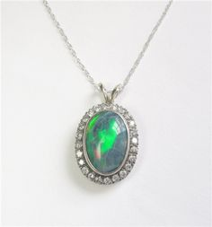 Opal and Diamond Pendant - This large and beautiful opal is surrounded by 0.50ct of diamond. The opal has a little crazing on the surface. The stones are set in 14kt white gold and platinum. K501048 (subject to prior sale) -- Lilliane's Jewelry -- 4101 W. 83rd St. Prairie Village, KS 66208 -- 913-383-3376 –