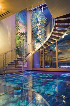 As soon as you walk in the door of this South Florida home you will have a complete sense of relaxation. When you step into the entryway you are literally walking on water. The 20-by-25-foot floor is covered in 3 inch starfire glass that has moving water beneath it. In front of you there is a 20-foot glass wall with water streaming down it and an LED light display. A hand-blown glass chandelier and a spiral staircase accent this wall.