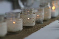 Burlap runner topped with lace-wrapped mini jars. Photography by iheartas.com