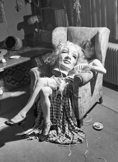 Young artist falls asleep with paper maché mask of Marlene Dietrich on her lap, 1950.