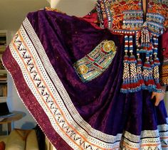 Beautiful vintage purple traditional Afghan tribal dress. This dress is hand sewn from the finest quality fabric, adorned with tiny beads, coins and gems. Purple velour and cotton sparkle with beads sewn into the material. Good vintage condition - as new. The front is adorned with orange and red embroidery, coins and tassles. This dress has a unique feature down one side: a turquoise, red and white pocket with turquoise beaded discs, mirrors and silver bells.