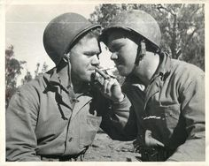 1943- U.S. Marine brothers, who served together on Guadalcanal, light up together somewhere in the South Pacific.