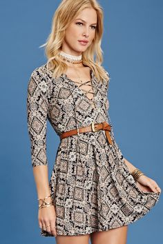 A stretch knit dress featuring an allover ornate print, lace-up front, 3/4 sleeves, a short length, and a flowy silhouette.
