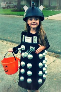 """DIY Dalek Costume Body was made from a black rectangular trash can (I cut the bottom out and turned upside down) Cut """"Ball Pit"""" balls in half and spray painted them silver - glued onto trash can body with hot glue gun. Used black elastic for shoulder straps. Kids craft foam paper for embellishments. Head was made from different small black flip trash can (padded with glued in socks haha). Eye stalk is a sink spray nozzle. Lights are plastic mouthwash cups."""