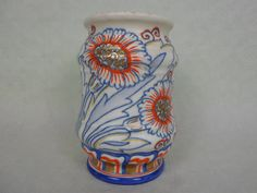 A 1930's Crown Ducal vase, designed by Charlotte Rhead in the Carnation pattern, no. 5924, featuring tube-lined daisies in blue, with gilt centres and red finish, printed and tube-lined marks to base (17.5cm).