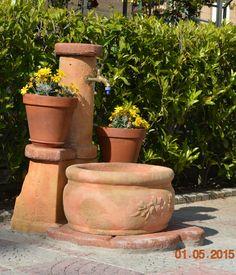 Fontana da giardino in pietra ricostruita modello: azalea, colore: pietre del borgo. Fontana con vasca grande e dettaglio floreale.