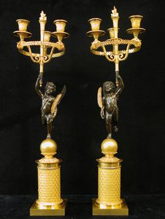 A fine pair of two gilt-bronze and patinated bronze three-light candelabra. The stems in the shape of a classical winged angel , holding a torch with flame, surmounted by three swan-shaped candleholders with leaf-cast nozzles and in the other hand a palmleave . Standing with one foot on a columnar socle on a square plinth. One of the holding palmets not original.<br> French, circa 1810.<br> Period : Empire.<br> Price : Euro 8.900.00
