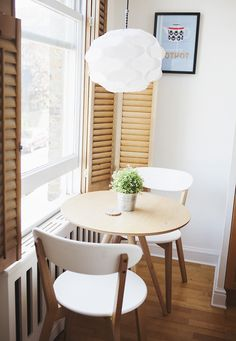 """Small (30"""") round kitchen Trifold table in blond wood, white matching chairs with walnut colored legs in the kitchen"""