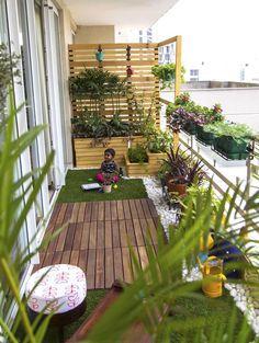 Aménager un balcon étroit avec brise vue en bois pin et sol en bois teck. Moquette en fausse pelouse, cailloux et multitude de plantes.