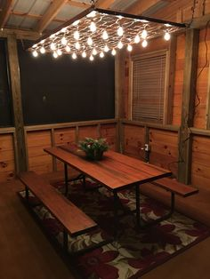 I love how our weekend project at the camper cabin turned out. This is a twin size bottom support springs for a mattress that we transformed into the cutest lighting over our picnic table on our screened porch. We used rusty chains to hang the spring mattress. We bought the Edison style string lights from Lowes. It took 3 sets of lights. #deckbuildingtips