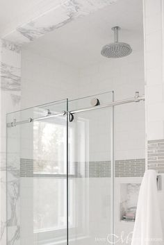 <3 Pin it and win a trip to New York, Barcelona, Berlin, Rome or London. - Glass doors on rail slides open to reveal a walk in shower filled with white subway tiles accented with a border of gray tiles alongside a marble tiled shower niche.