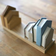 dos-à-dos binding of 5 books to look like a row of houses, with a nice matching wood shelf with identical row of wooden houses.