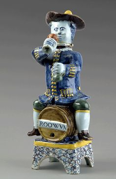 Delft Polychrome wine jug. Importante fontaine de table anthropomorphe représentant un personnage traité en polychromie dont la tête amovible figure le couvercle. Il est assis à califourchon sur un tonneau marqué « Roowyn » (vin rouge) posé sur un socle marbré. Il tient d'une main un gobelet et de l'autre une bouteille. XVIII°siècle. Haut : 35,5cm.