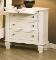 The #Sandy Beach White Nightstand by Coaster (model - 201302) is a beautiful white hardwood nightstand with three drawers and a pull-out tray. Like the other pie...